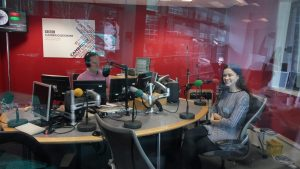 Radio studio with Lucy sat behind a microphone opposite Jeremy whilst live on air