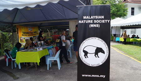 Stalls Lined Up Behind A Malaysian Nature Society Banner Featuring A Tapir